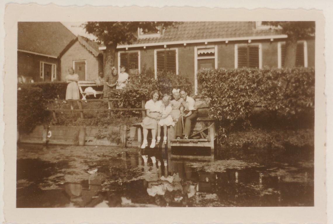 Fotoalbum Andre Kamsma, 033, Fam. Kamsma oan de âld feart foar it hûs fan Hieke en Otje Palsma neist Doeke en Trude Schaafsma, rûnom 1950